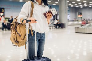 Woman backpacker holding passport and map with suitcase standing at check in baggage at airport terminal,traveler concept.